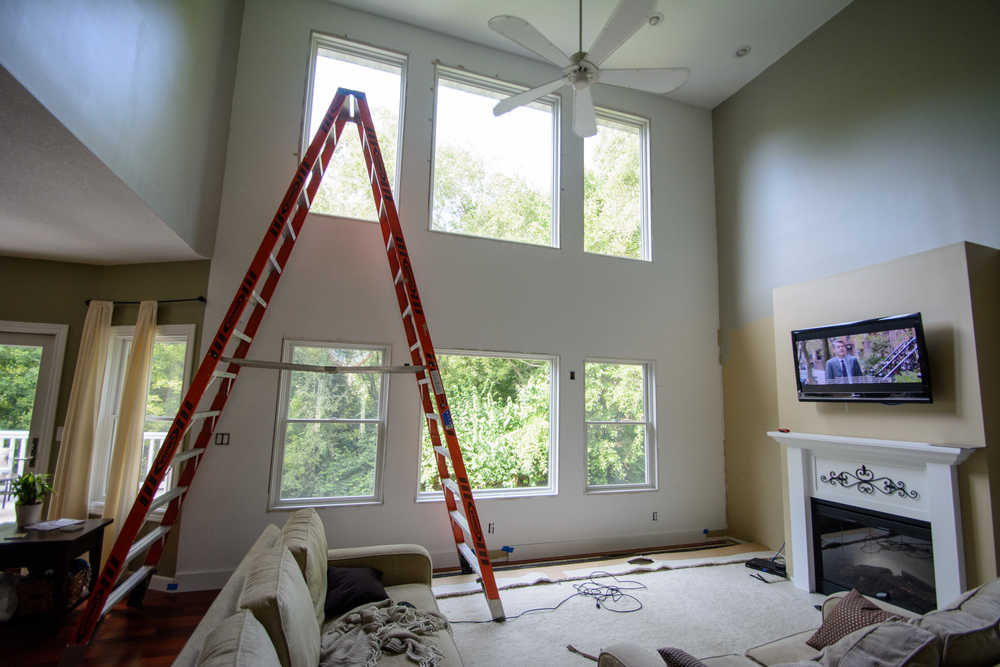Adding molding to a two story living room wall.