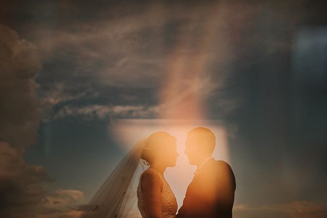 Triple exposure! How it's done:  1. base shot of couple, almost silhouetted against sky (expose for sky), making sure to isolate them in the sky by shooting from down low to crop out background trees  2. Picture of candle burning + a prism, slightly blurred and used to highlight couple  3. Took that double exposure as the new base and then shot a close up picture of a funky bright art work-also blurred- for the rainbow effect. The white triangle shape came from a reflection in the art work shot.  Hope that makes sense, feel free to ask questions below!!