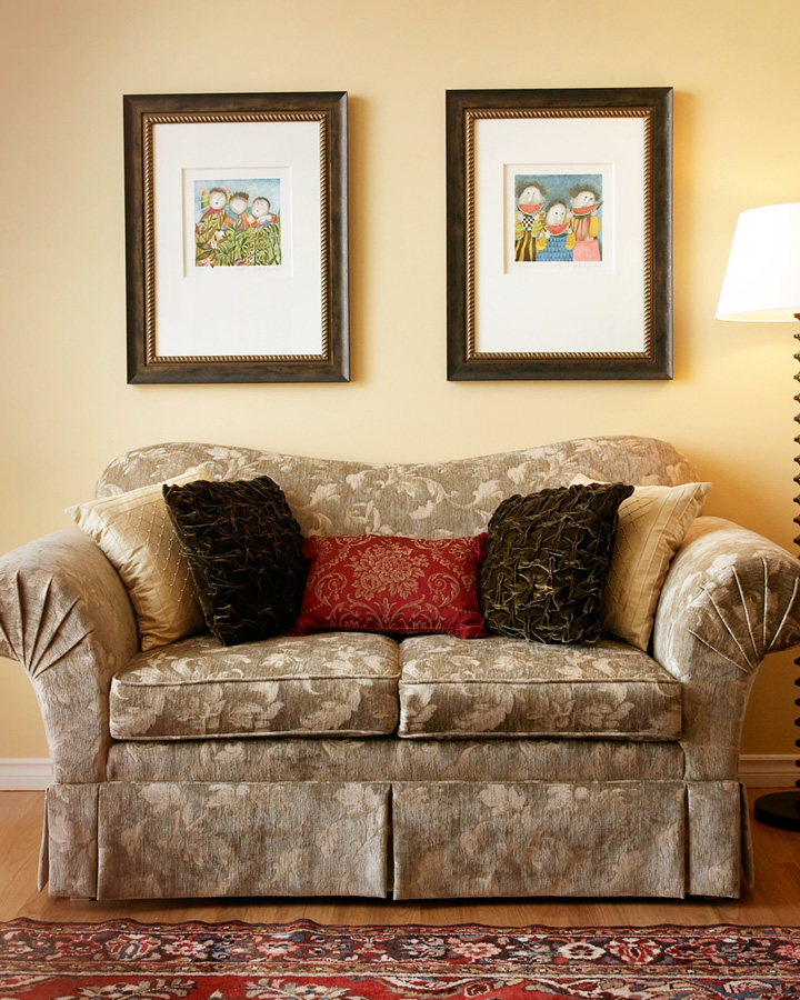 IDEAL HEIGHT TO HANG FRAHMES   A common mistake is to hang artwork too high. Here the work is 4 to 6 inches above the back of the couch. Don't let the artwork spill over the edge of the couch. Your sofa should be wider than your artwork!