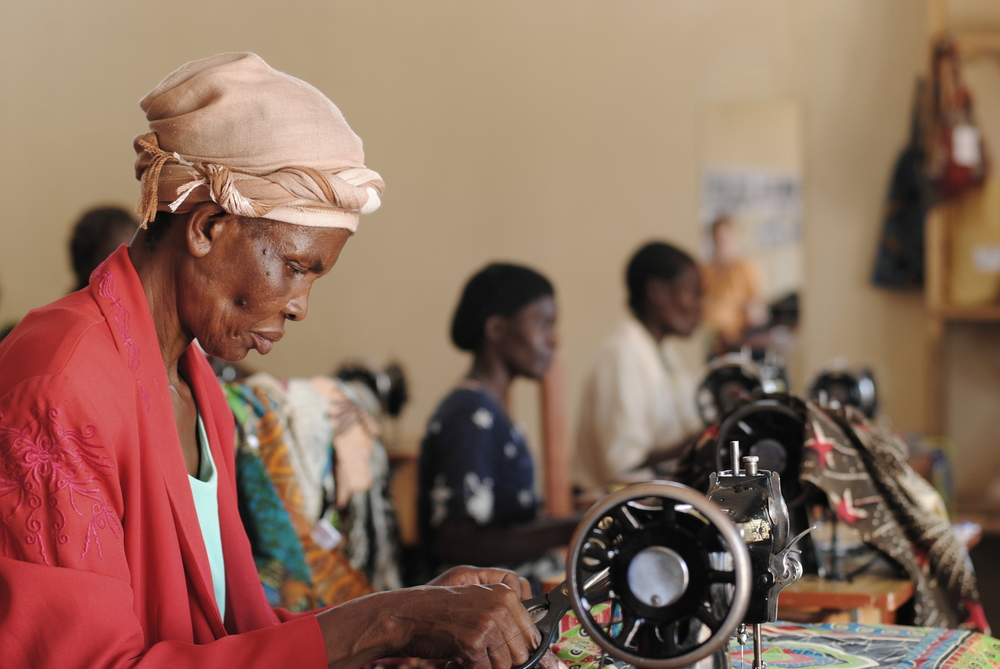 Ruth, a member of the sewing collective, works on sewing a dress.