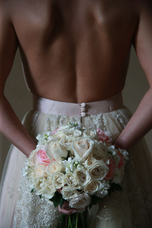 Here the bride is holding the bouquet behind her back.  It's really powerful when the wedding gown is backless and the hands are hidden.
