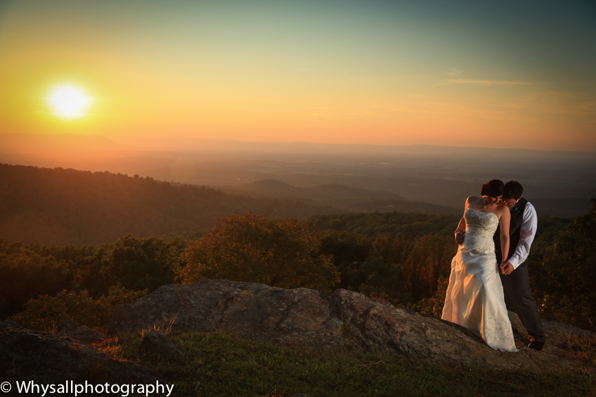 Dramatic sunset shot of bride and groom at sunset. Notice the bride and groom are off center, and this photo doesn't need a foreground frame.  The bride and groom are the focus of the shot.