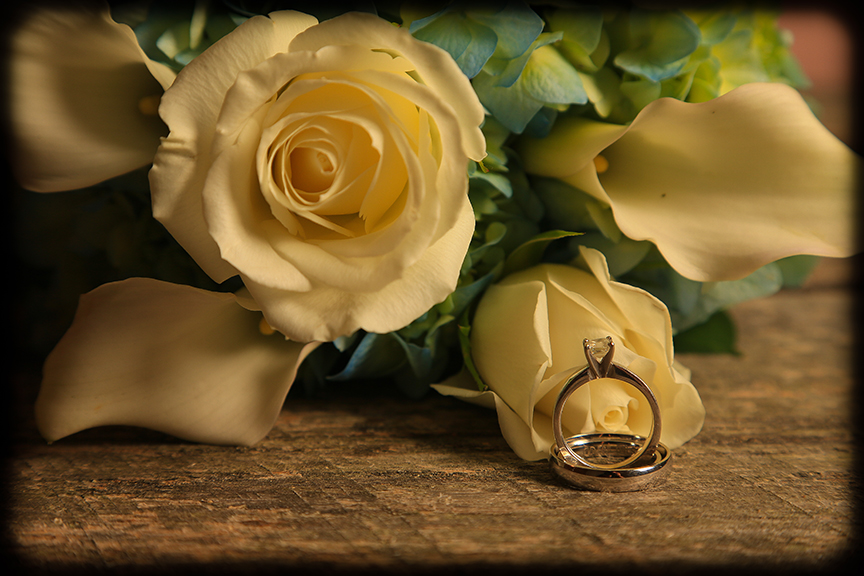 wedding rings and bouquet in photo studio