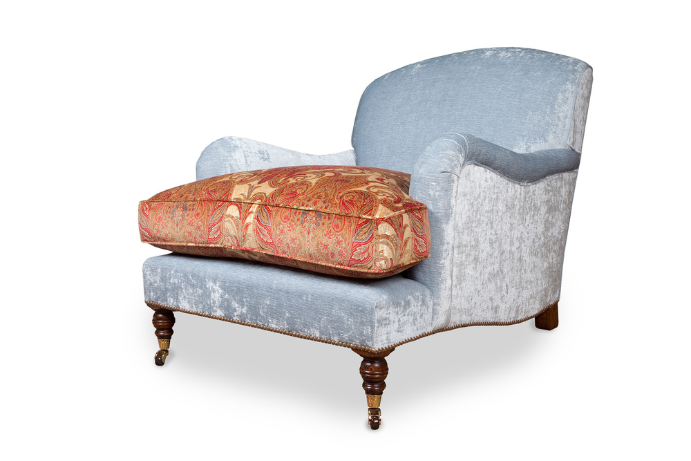 """Howard"" armchair  with brass and brown ceramic castors, feather down cushion and lower rail contours  trimmed with individual antique brass nail heads"