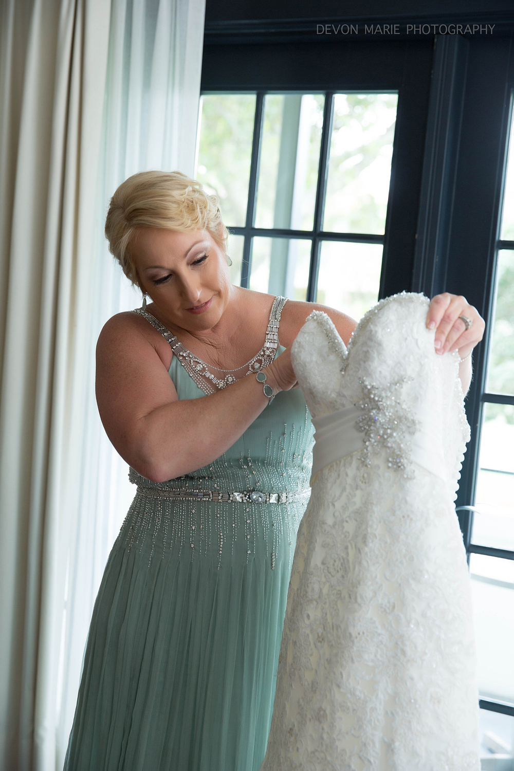 Her mom admiring her little girls wedding dress...