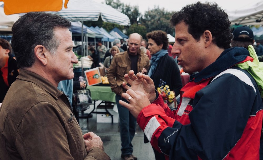 "With Robin Williams on the set of the Farmer's Market.   Robin was the most emotionally vulnerable and available person I've ever met. A true artist, a born performer. What can I say about him that hasn't been said a thousand times before. He insisted on calling me ""Boss"", and was a fountain of great ideas. When he suggested a line change (which was invariably better that what we had) he would press to first play the line as written, then his alternative, so that we had a choice in the editing room if we needed it. Heartbreaking to think of all the incredible performances we'll never get to see."