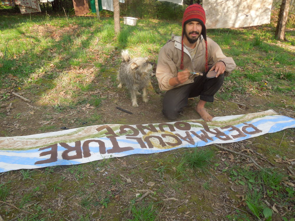 Our volunteer Ando making the sign for the Permaculture Lounge. He still has a lot more he wants to do, but it's looking great! His assistant Lolli trying to help out.
