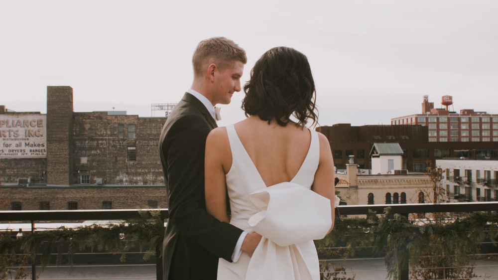 Luke holding Kristin on balcony while looking down into the busy city streets