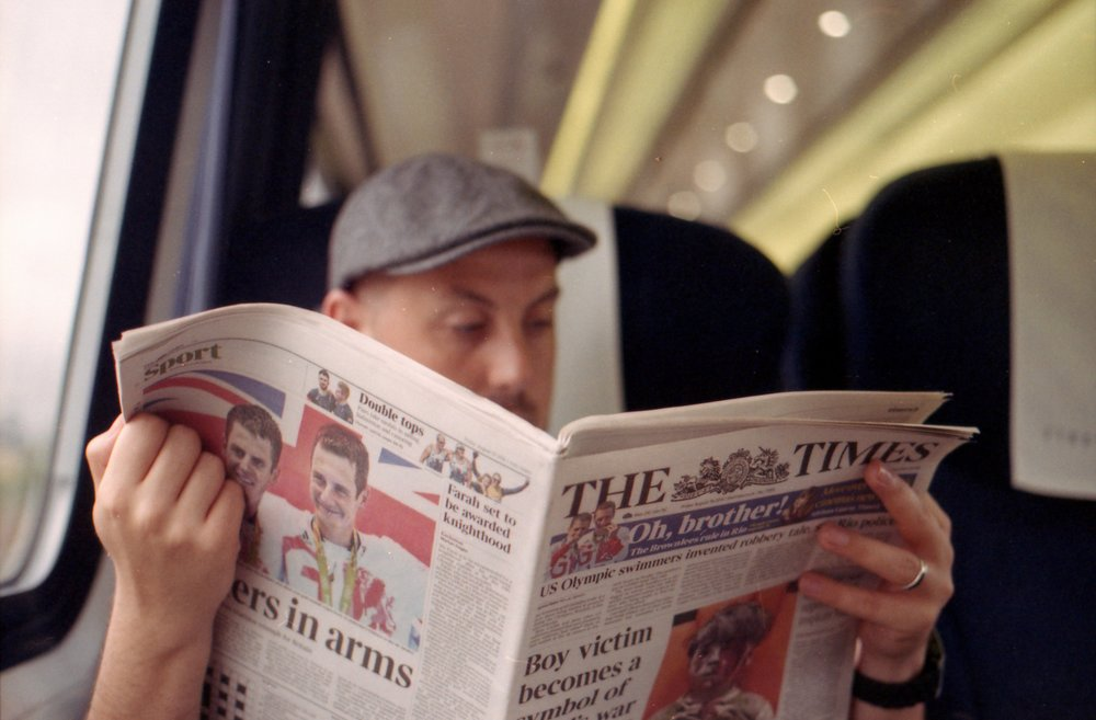232/366 - My husband reading the free paper on the train. I'm quite taken with him.