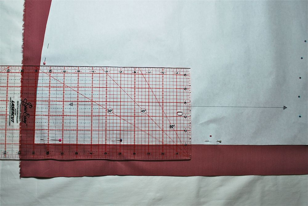 See above how the straight line of the grain line arrow is positioned parallel to the lines on the quilting ruler.