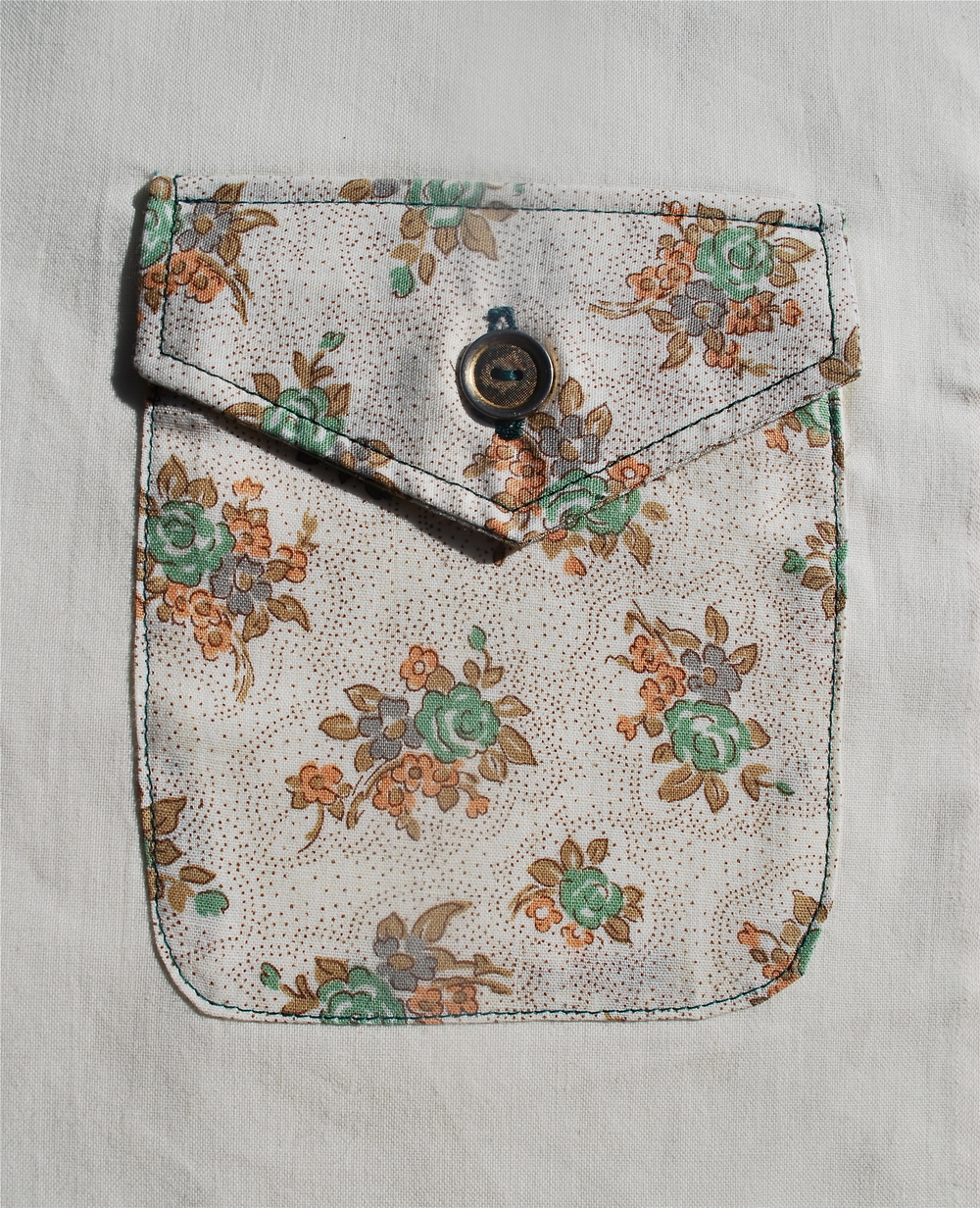 A patch pocket with a flap, a button and rounded corners. This one is from the Colette Negroni pattern.