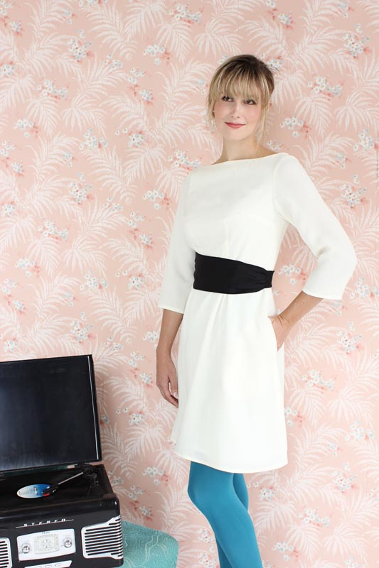 PEONY Colette This elegant bateau neck sheath dress is simple to sew, with added interest from a fully removable cummerbund style belt which can be made in a matching or contrasting fabric, closing with a single button in back. Version 1 has 3/4 length sleeves, a contrasting belt, and in seam pockets. Version 2 has short sleeves, a matching belt, and no pockets.