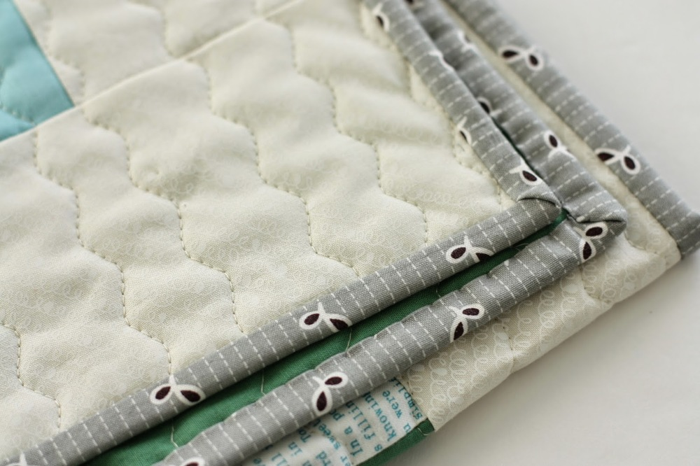 Grey striped binding on the edges of a quilt.