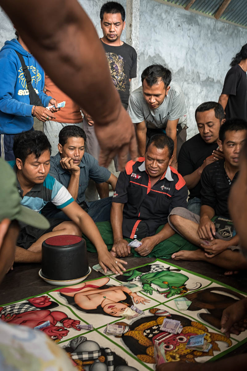 Tajen spectators taking part in small stake games before proper betting starts.