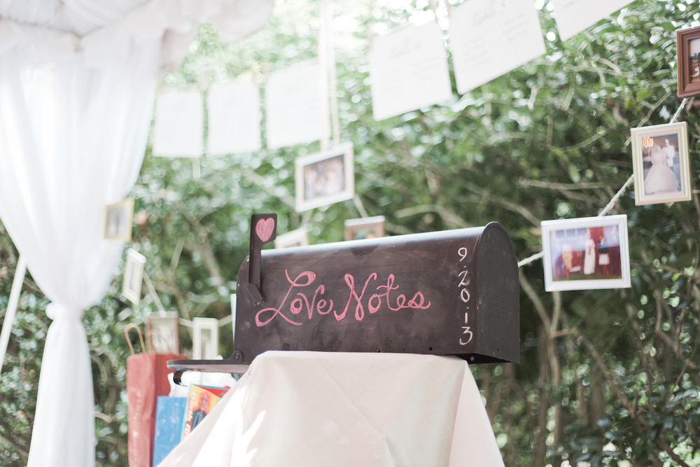 A whimsical mailbox sits atop a vintage lace tablecloth.