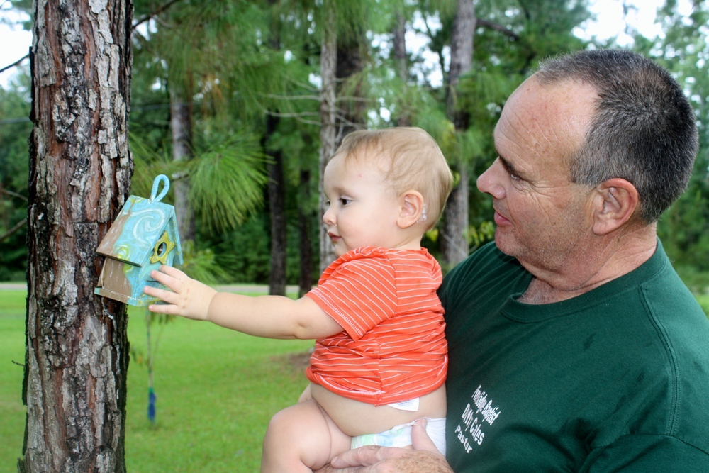 Judah with his grandad checking out the birdfeeder I painted last spring break.
