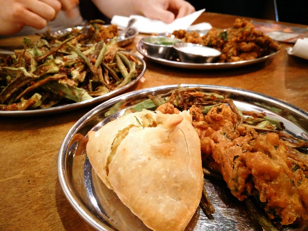 Pillowy veggie samosas, crispy kale pakoras, and salty-limey okra fries from Chai Pani