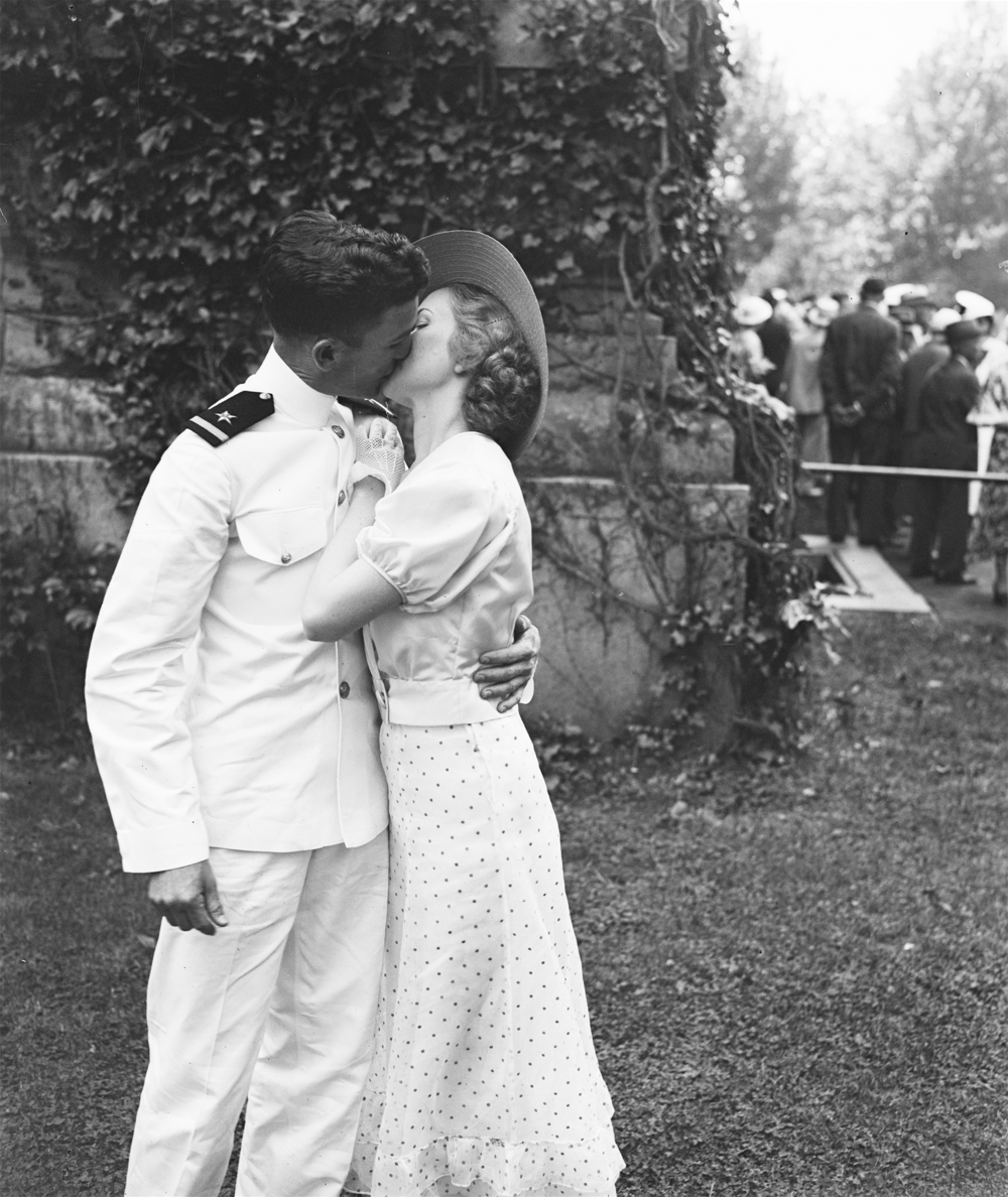 Colorization the 1934 image: A kiss of congratulations. W.F. Cassidy of Forth Worth, Tex., one of the 463 graduates of the United States Naval Academy at Annapolis today, receives a kiss of congratulations from his sweetheart Helen Fisher of Annapolis, Maryland. May 1934