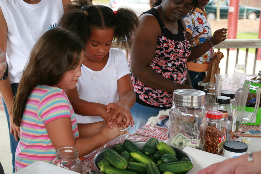 """""""Farmer Foodshare to TABLE"""" kids learning to make pickles as part of the Carrboro Farmers' Market's """"Year Round Food"""" Community Canning Series!Photo courtesy of Kelley Breeze."""