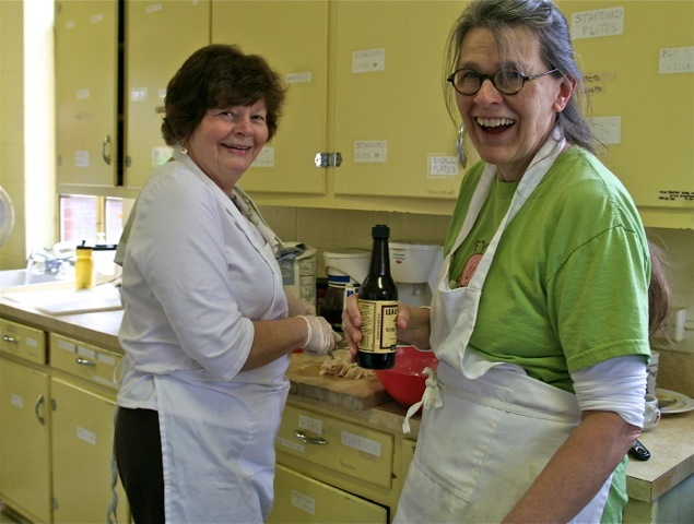 Karen Ladd and a Volunteer preparing the lunch and having fun doing it.