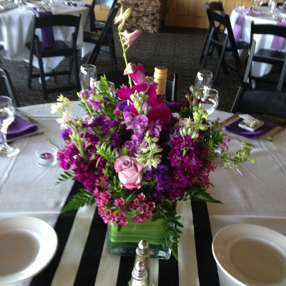 "Cool Water Roses, Purple Stock, White Larkspur and Purple Wax in a 5"" glass square vase wrapped in Ti Leaf."