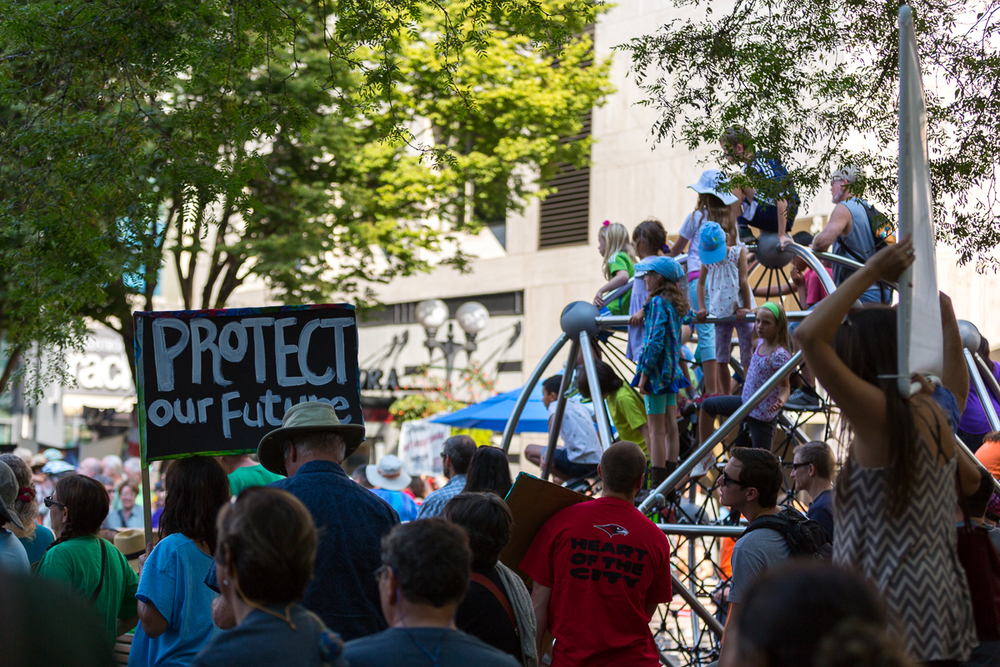 Adults listen to the speakers at a people's Climate rally in Seattle, WA. Meanwhile, children climb up high to get a view of the speaker and the crowd.  September 21, 2014.