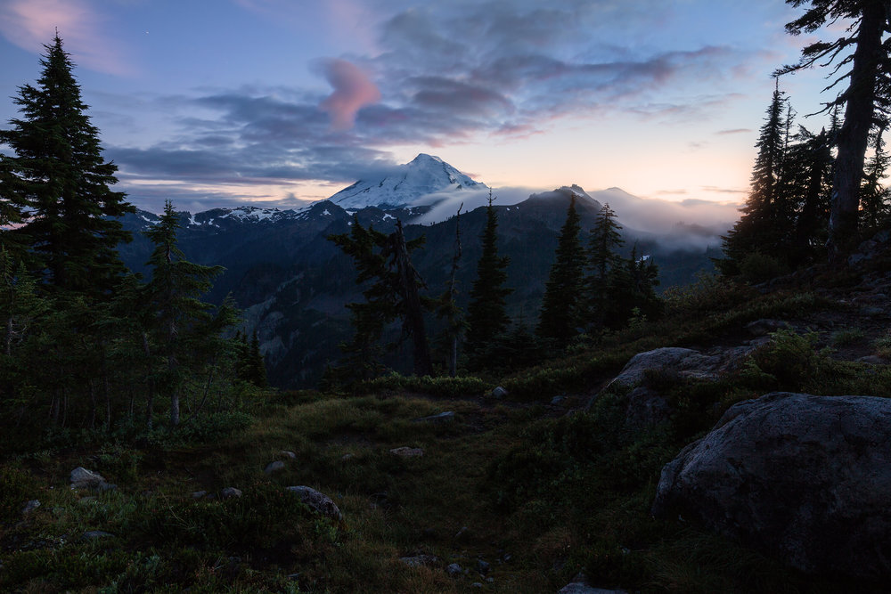 Mount Baker is consumed by twilight. The sun still illuminates the horizon in the distance.