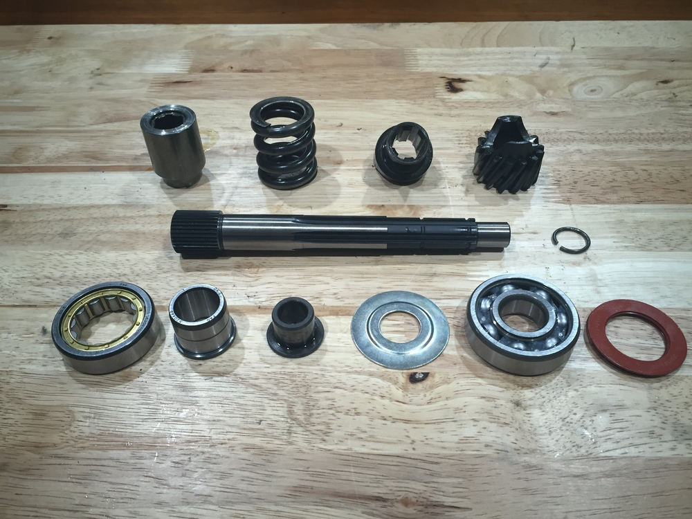 After the snap ring is out, the shaft can be completely disassembled. The new parts include; drive shaft, Japanese made groove bearing, bearing cover plate, and cylindrical roller bearing.