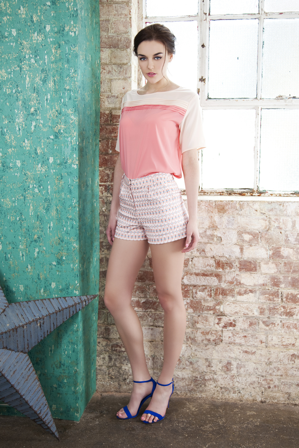 Geometric shorts styled with the peach and pink pleated panels  top.