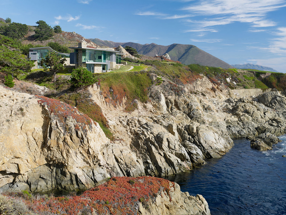 Perched atop a rocky outcrop overlooking the ocean, this Carmel residence strives to appear as a natural extension of the landscape while resolving competing private and public concerns.  The large area of the house is disguised by splitting the house into two wings.  Stone cladding predominates, rooting the house in the site and visually connecting with the rocky cove.
