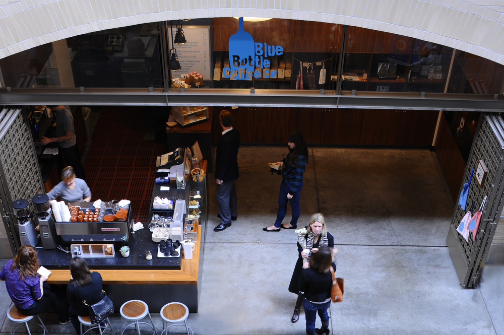 Opened in 2005 in the garage of Sagan Piechota's Linden Street studio, BLUE BOTTLE COFFEE has gone on to open coffee houses all over the country including this kiosk at the San Francisco Ferry Building where a bustling crowd of tourists and locals pass through for their daily brew.