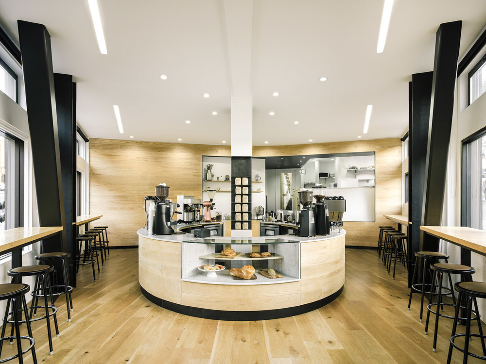The distinctive circular counter at the Reveille Coffee House in North Beach plays contrast to the sharp  flatiron corner where it resides at Kearny and Columbus Streets.  The overall mix of white and black finishes, combined with blonde woods reflects the brand's stylish urban aesthetic.