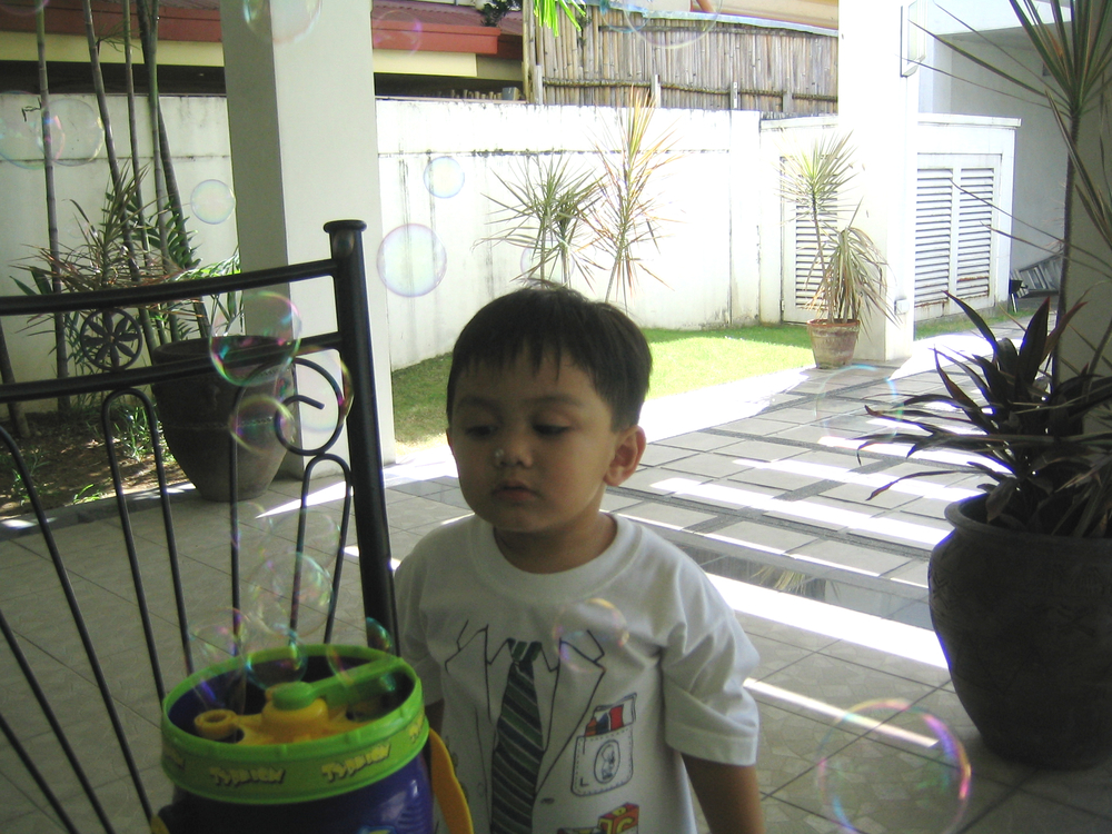My son studying his brand new bubble machine in  lola's  (grandma) house.