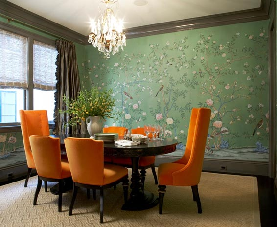 massucco-warner-miller-dining-room-oval-table-crystal-chandelier-bird-green-wallpaper-orange-upholtered-dining-chairs.jpg