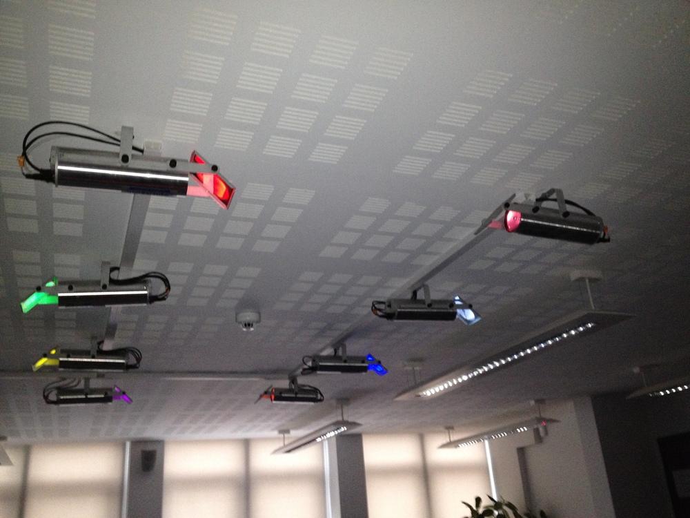 Lyskastere i taket sender lysstråler ned på gulvet.