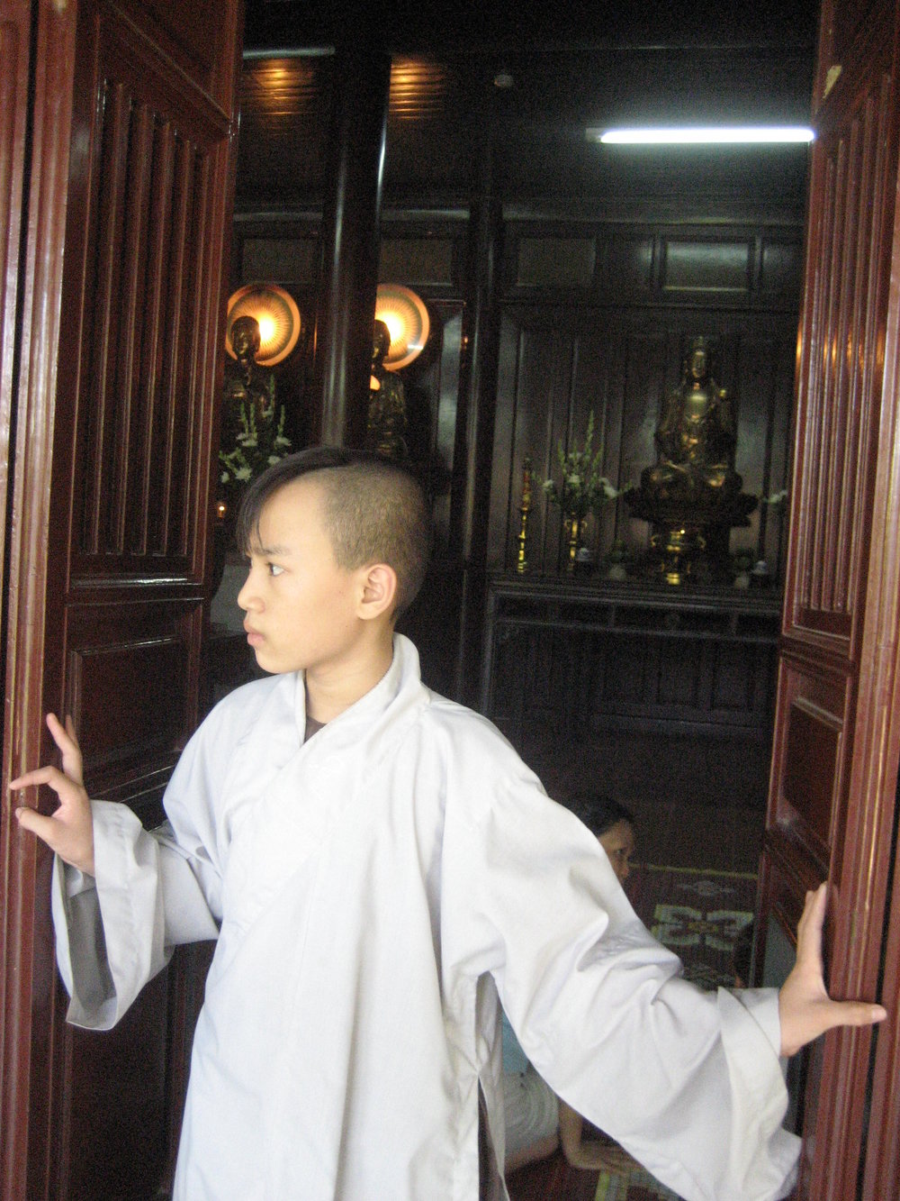 A monk in training, and the awful haircut that is required.