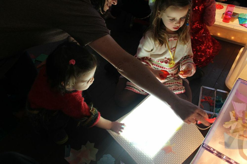 Parents and children explore light together.