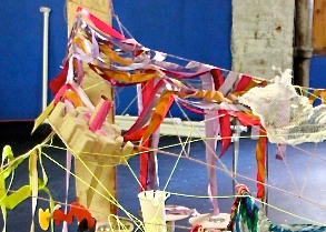 Yarn creates a ceiling. Paper and cardboard balance and float upon the weblike structure of the children's fort.