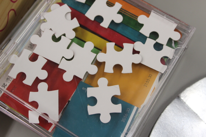 A cd full of puzzle pieces on top of a cd full of colorful paint chips and sticks.