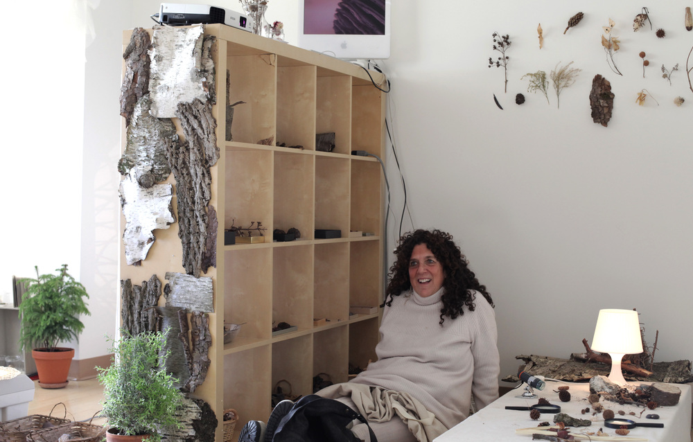 "The illustrious Linda White, dressed in white, engaging with visitors in a beautiful white room called the Natural Materials Atelier. Here is the room in its first mood, ""Forest."" It went on to become transformed, thanks to the work of Robin Koo, into ""Ocean"" and ""Plants."" Linda was one of the many NYC-based educators who volunteered to set up and maintain the ateliers and show visitors around."