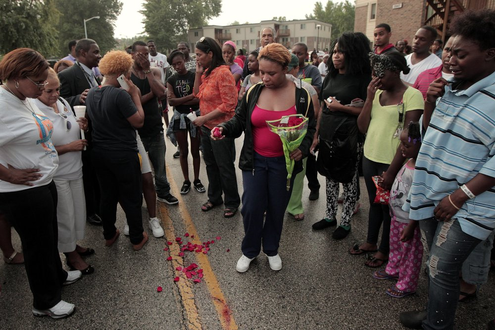 Lesley McSpadden (center) drops rose petals on the blood stains from her son who was shot by police in the middle of the street earlier in the afternoon in the 2900 block of Canfield Drive on Saturday, Aug. 9, 2014, in Ferguson.   Photo by Huy Mach, hmach@post-dispatch.com