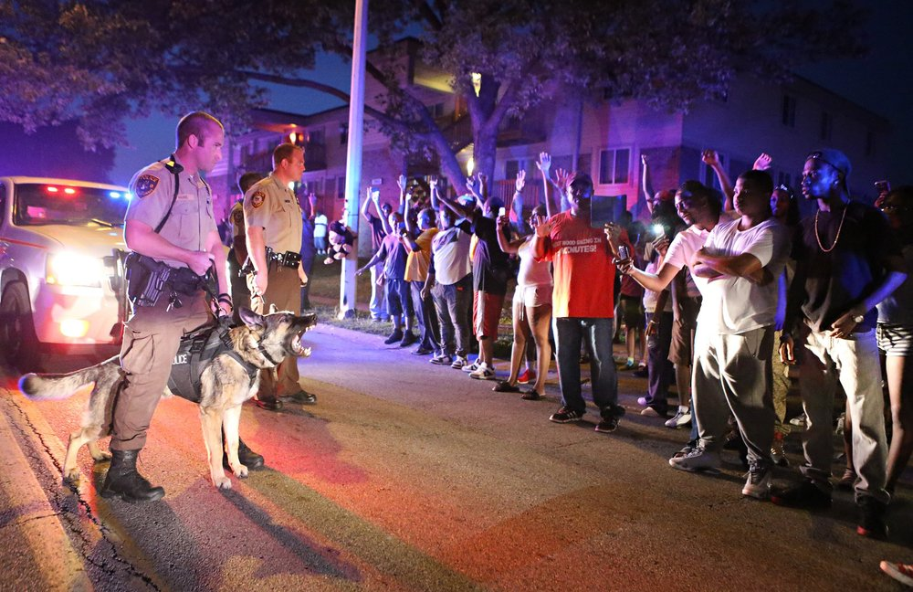 Police officers stand to confront a crowd they're trying to break up a on Canfield Dr. in Ferguson on Saturday, Aug. 9, 2014. Earlier in the day police had shot and killed an 18 year-old man on the street and the crowd of people were upset.   Photo By David Carson, dcarson@post-dispatch.com