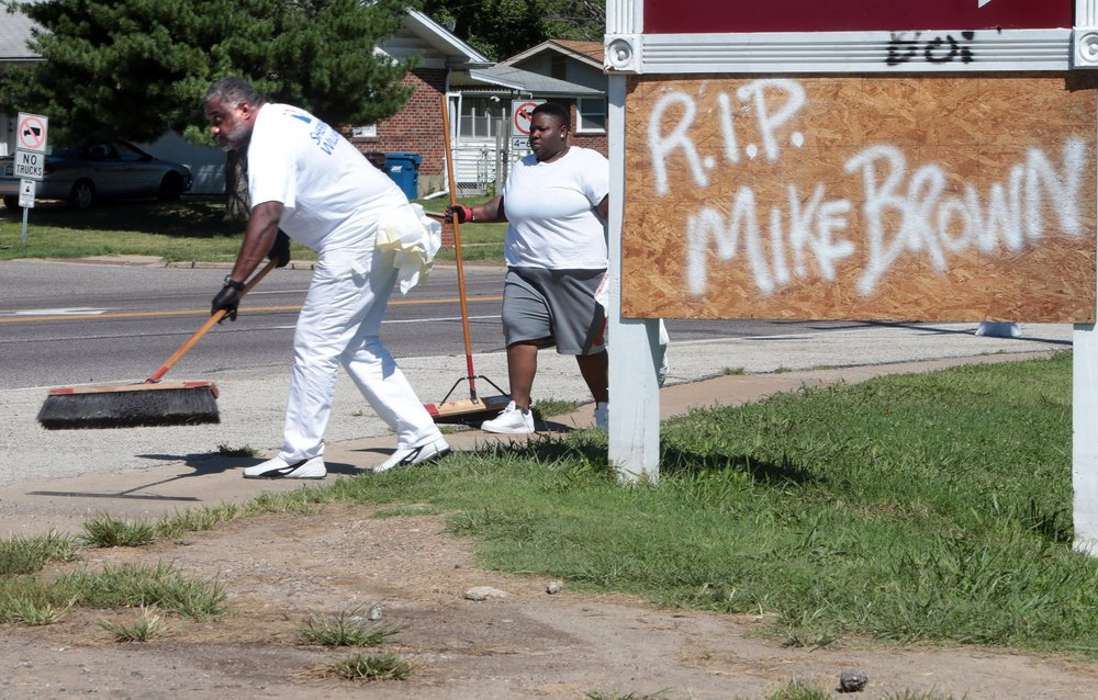"""I wanted to come out and help bring this community back together. And with being older, I wanted to set an example and inspire leadership to the youth,"" said Anthony Clark of Arnold (far left) who helps clean up trash on Wednesday, Aug. 13, 2014, on W. Florissant Ave. in Ferguson. More than 100 volunteers came together to send a positive message to the community by cleaning up the businesses and areas that were damaged by looting and riots on Sunday night. Behind Clark is volunteer Keeosha Conely of Ferguson.   Photo by Laurie Skrivan, lskrivan@post-dispatch.com"