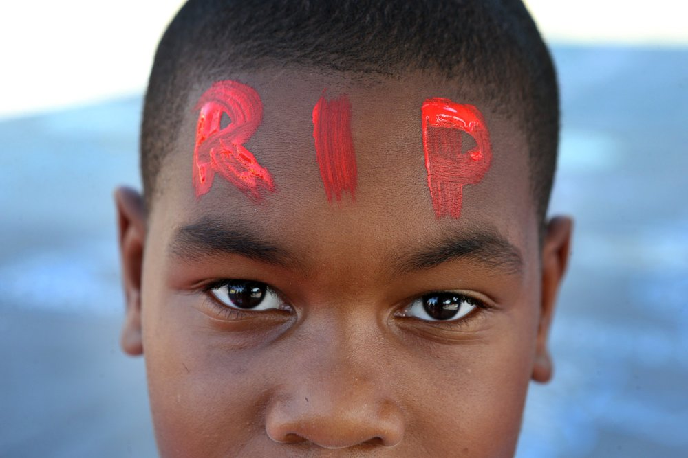 Jordan Puckett, age 10, shows off his painted forehead honoring Mike Brown during a gathering of people on the QuikTrip lot on Thursday, Aug. 14, 2014.   Photo By David Carson, dcarson@post-dispatch.com