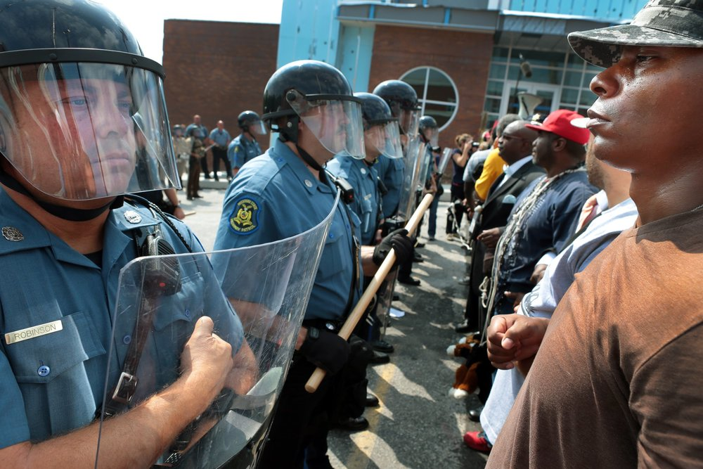 Protester Boss Bastain of St. Louis locks arms with others as they confront Missouri State Highway Patrol troopers in front of the Ferguson police station on Monday, Aug. 11, 2014. Marchers are entering a third day of protests against Sunday's police shooting of Michael Brown.   Photo by Robert Cohen, rcohen@post-dispatch.com