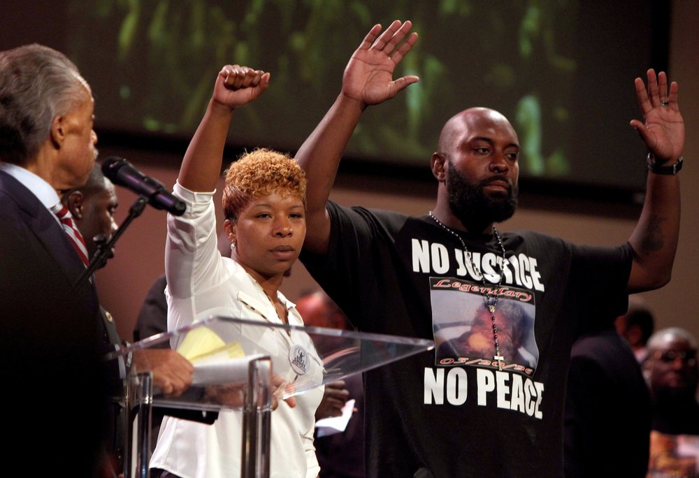 Lesley McSpadden (center) and Michael Brown, Sr., the parents of Michael Brown raise their hands to acknowledge support during a rally at Greater St. Mark Family Church in Florissant on Sunday August. 17, 2014. Protests an anger have broken out in the Ferguson community since Michael Brown, an unarmed teen, was shot by Ferguson police officer Darren Wilson last Saturday.   Photo by Christian Gooden, cgooden@post-dispatch.com