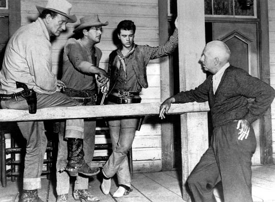 (from left to right) John Wayne, Dean Martin, Ricky Nelson and Director Howard Hawks on the set of  Rio Bravo