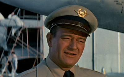 John Wayne as Dan Roman in The High and the Mighty (1954) whistles the main theme composed by Dimitri Tiomkin.
