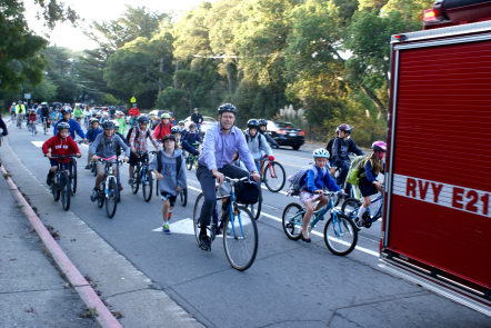 Former Manor School principal, Jason Richardson, leads a pack of kids to school on International Bike and Walk to School Day.