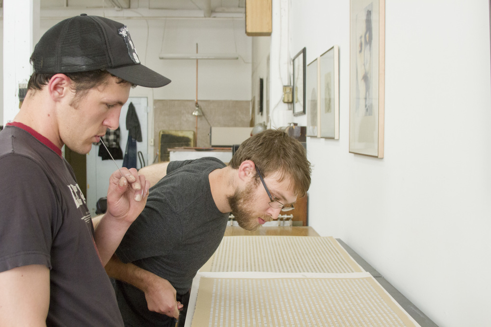 The artist and the printer reviewing a proof